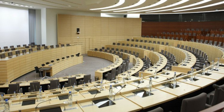 grote cirkelvormige conferentiezaal met voor iedere zitplaats een tafel met leeslamp en microfoon