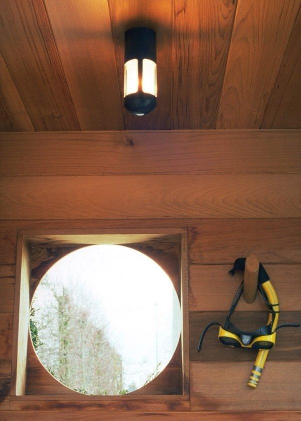 plafondlamp in houten kleedhokje buiten zwembad
